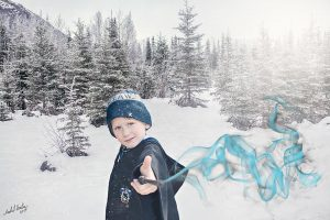 Little boy in Ravenclaw robes in snowy area with trees and a mountain making magic come out of his wand that's pointed at the viewer.